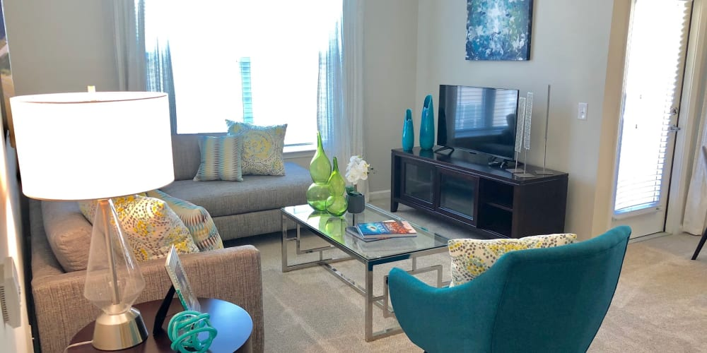 Modern furnishings and large bay windows in a model home's living area at Level at 401 in Raleigh, North Carolina