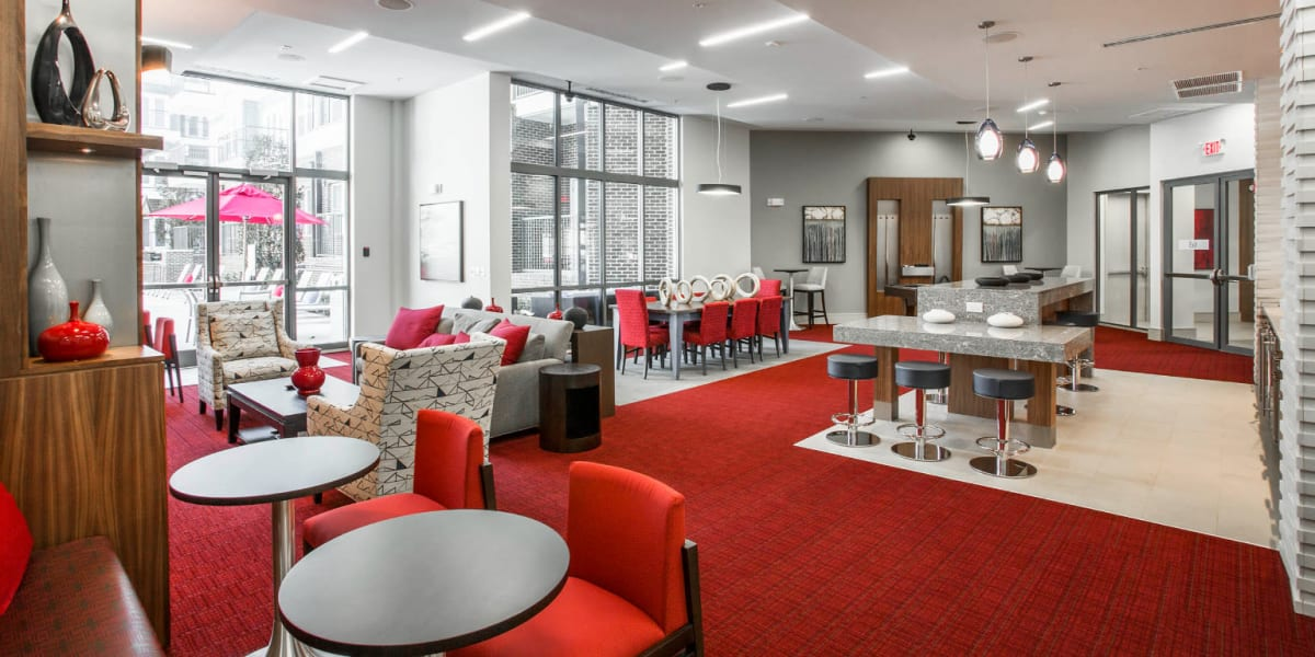 Large colorful community room with dining, kitchen, pool, and sitting areas at Marq Midtown 205 in Charlotte, North Carolina