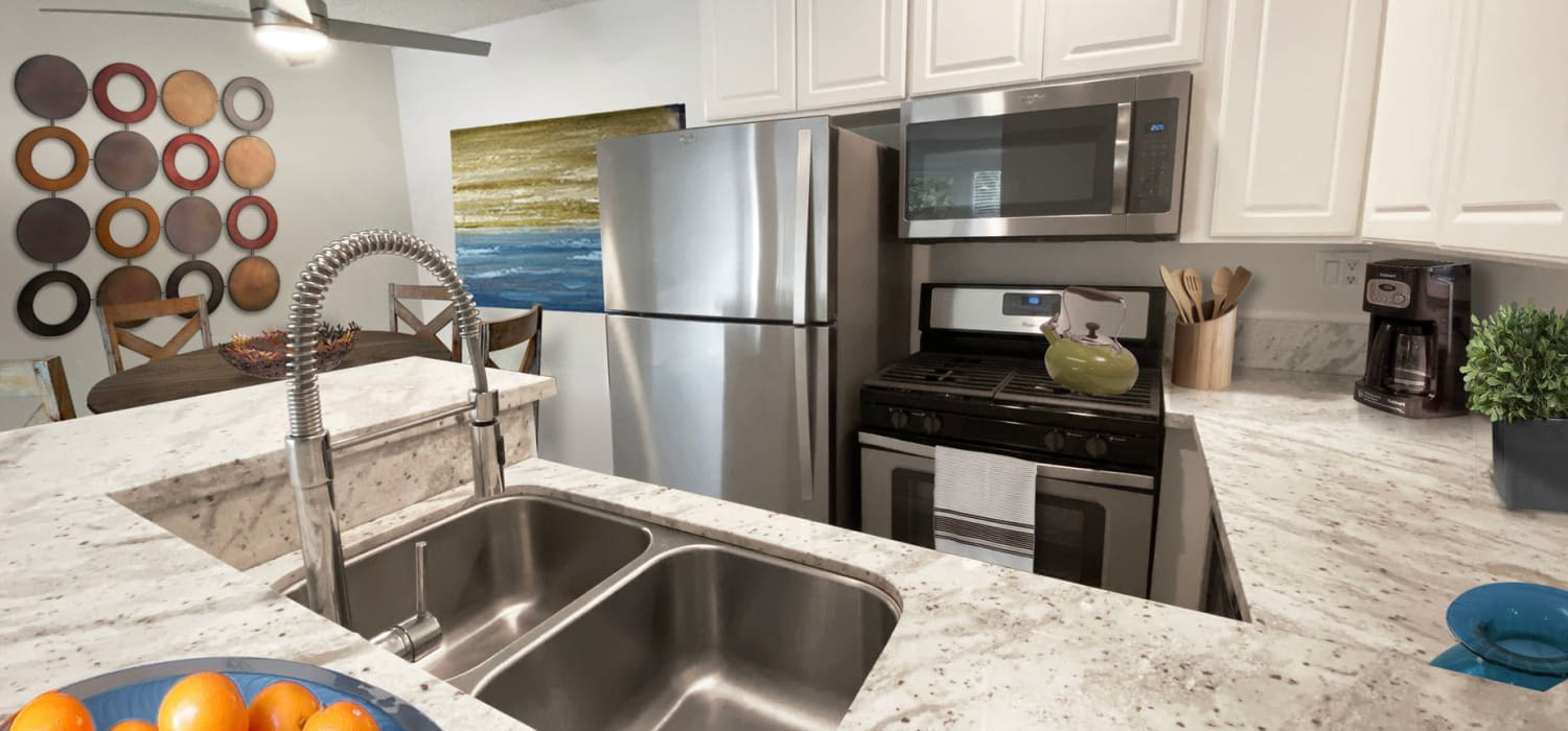 Beautiful chef-inspired kitchen with granite countertops in a model classic apartment at Sunset Barrington Gardens in Los Angeles, California