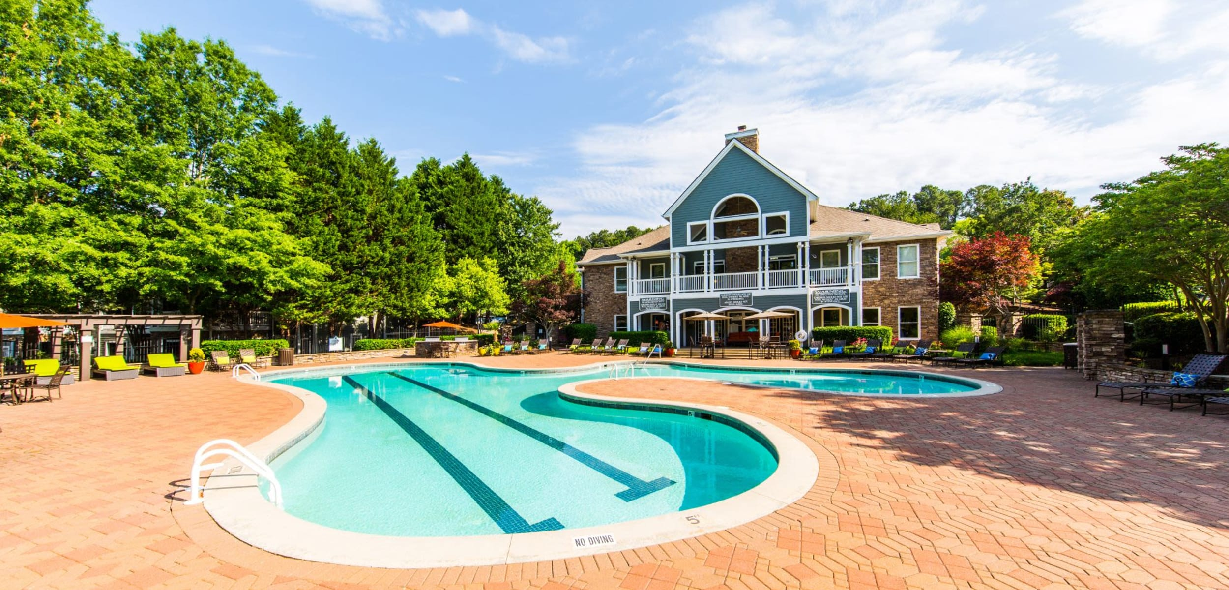 Bright pool with the clubhouse in the background at Marquis on Edwards Mill in Raleigh, North Carolina
