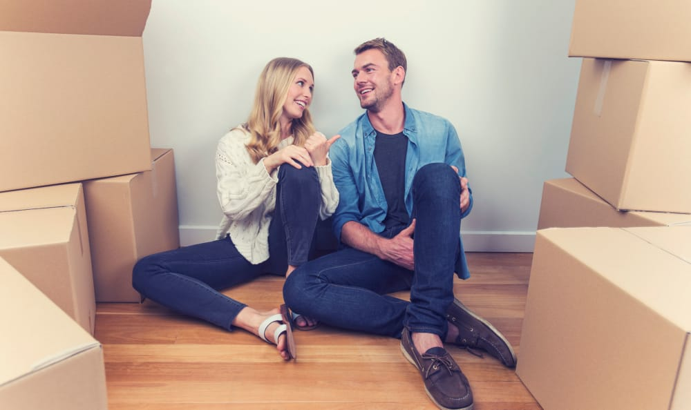 Couple sitting on the floor surrounded by moving boxes near Superior Storage