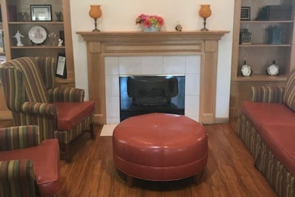 Welcoming resident sitting room with fireplace at Ramsey Woods in Cudahy, Wisconsin.