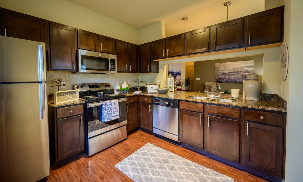 Kitchen with dark wood cabinets and wood style flooring at Pecan Springs Apartments in San Antonio, Texas