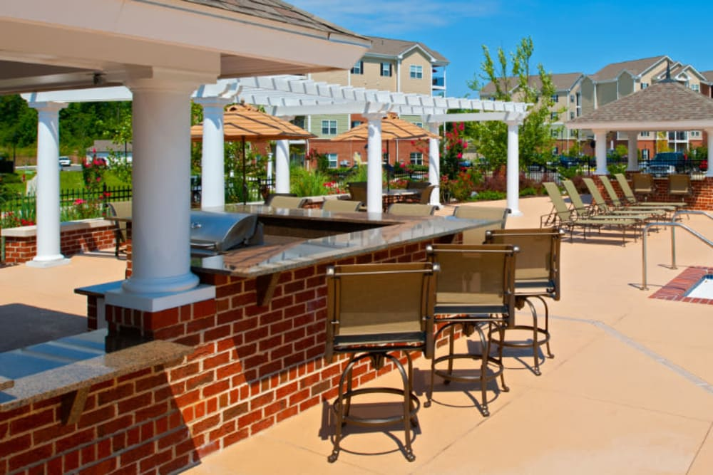 A barbeque area with bar seating next to the pool at Meridian Watermark in North Chesterfield, Virginia