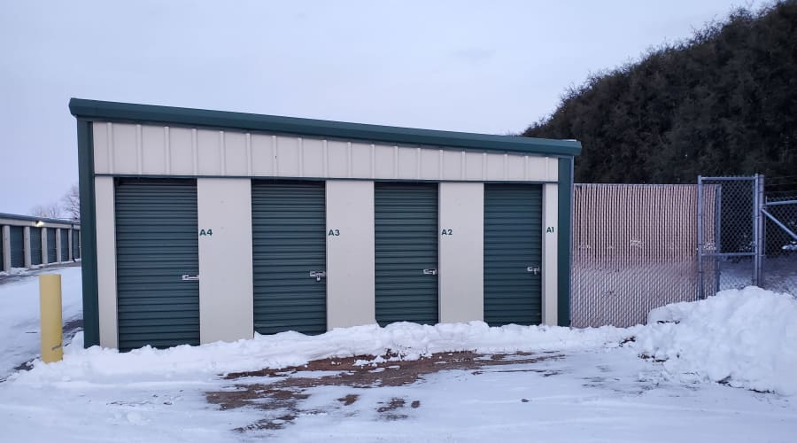 Outdoor storage units with green doors and trees in the background at KO Storage of Willmar in Willmar, Minnesota