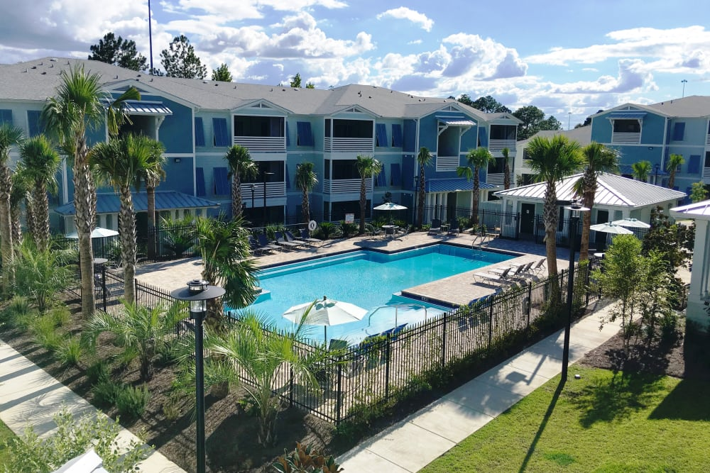 The community exterior and gated pool at West Woods Apartments in Pensacola, Florida