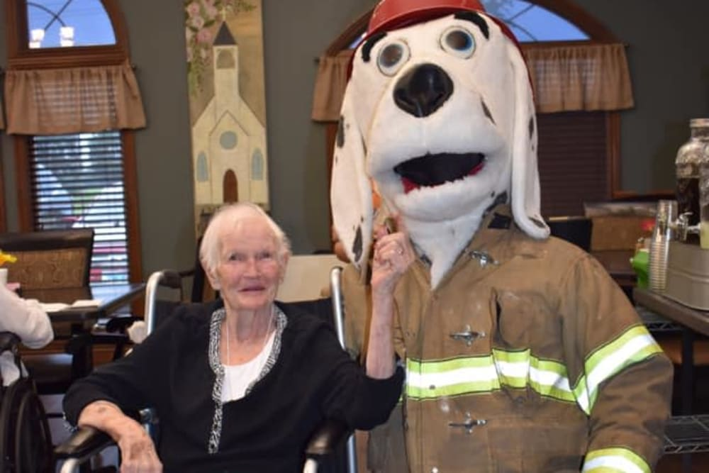 A resident being greeted by a firehouse dog mascot at Villas of Holly Brook Marshall in Marshall, Illinois