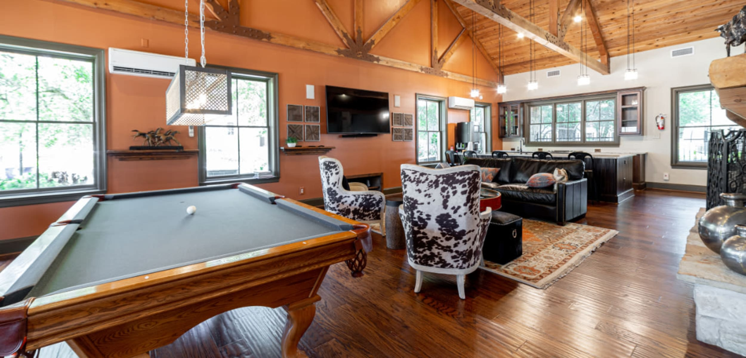 Pool table, seating area, and kitchen in rustic clubhouse at Marquis at Bellaire Ranch in Fort Worth Texas,