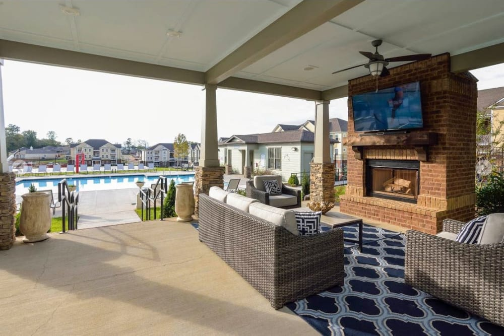 Covered outdoor lounge with a fireplace and flatscreen TV at The Retreat at Arden Village Apartments in Columbia, Tennessee