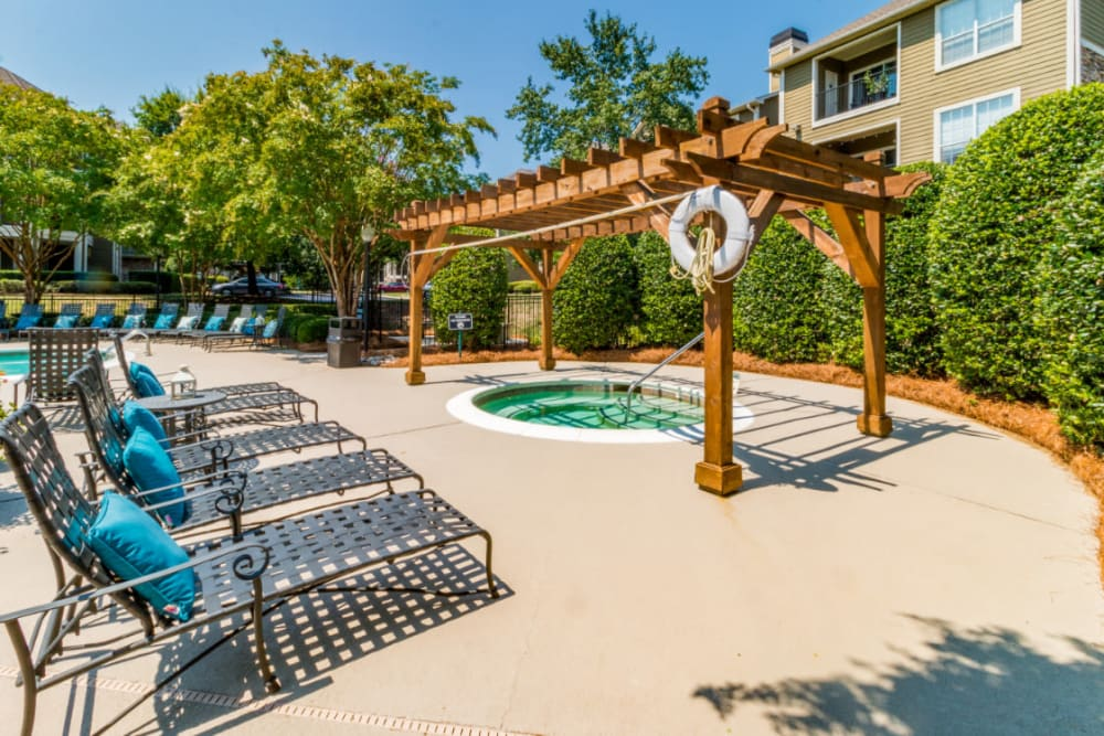 Partially shaded hot tub area with lounge chairs at Marquis at Carmel Commons in Charlotte, North Carolina