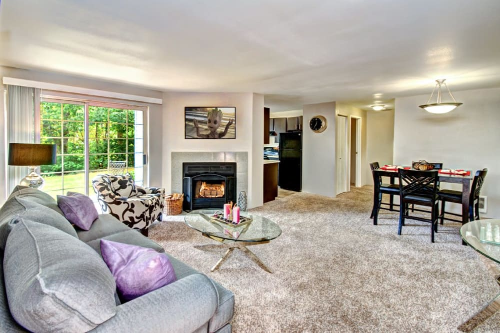 A spacious living room and dining room with private patio access at Wellington Apartment Homes in Silverdale, Washington