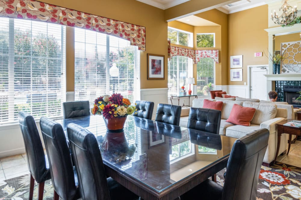 Community clubhouse sitting area with dining table and chairs, sofas, and large windows at Marquis of Carmel Valley in Charlotte, North Carolina