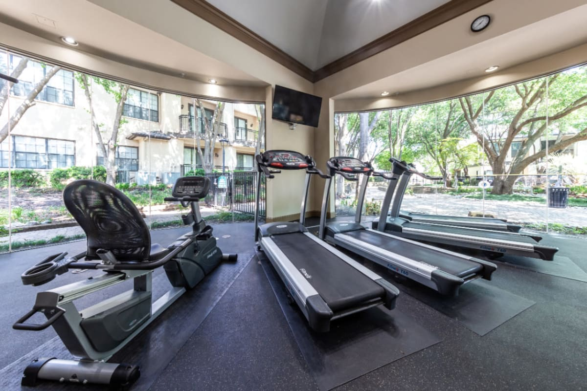 Sitting exercise bike and treadmills with view of the pool deck at Marquis at Waterview in Richardson, Texas
