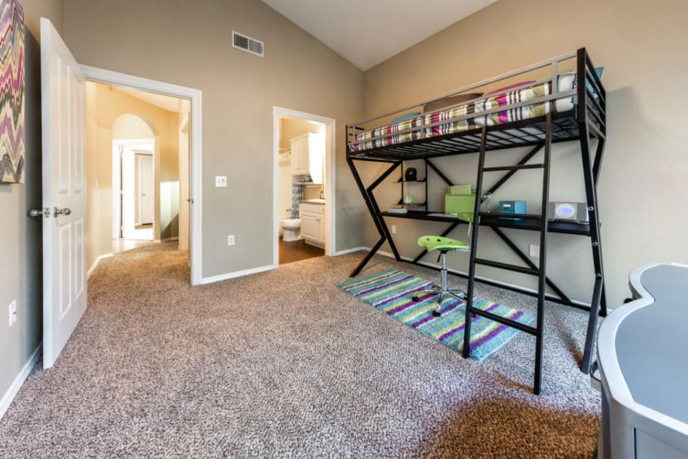 Carpeted bedroom with private bathroom and vaulted ceilings at Marquis at Waterview in Richardson, Texas
