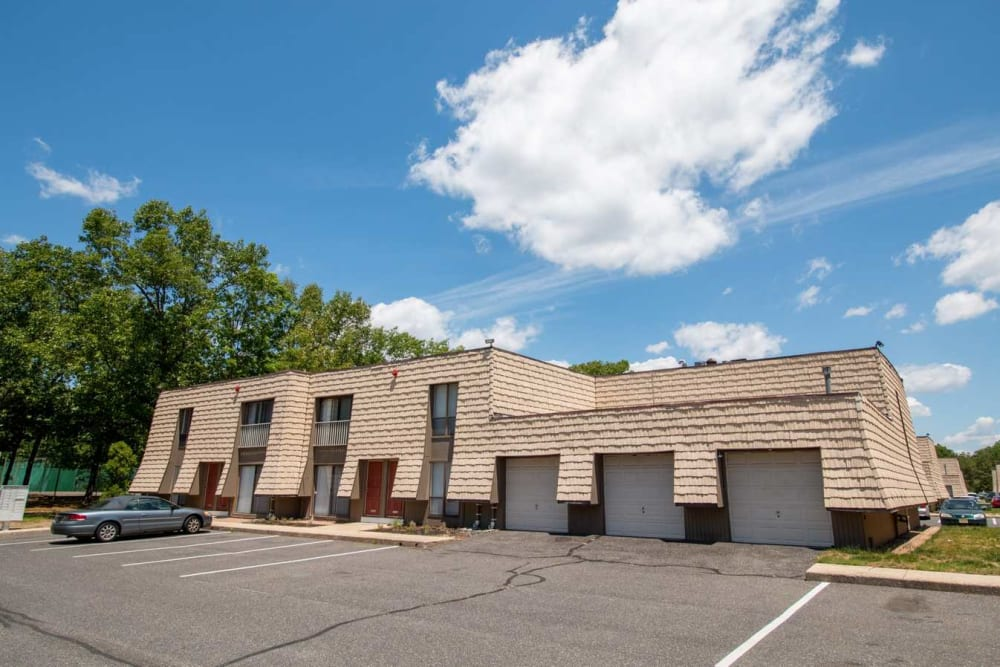 Exterior of an apartment building with detached garage parking at Mill Village in Millville, New Jersey