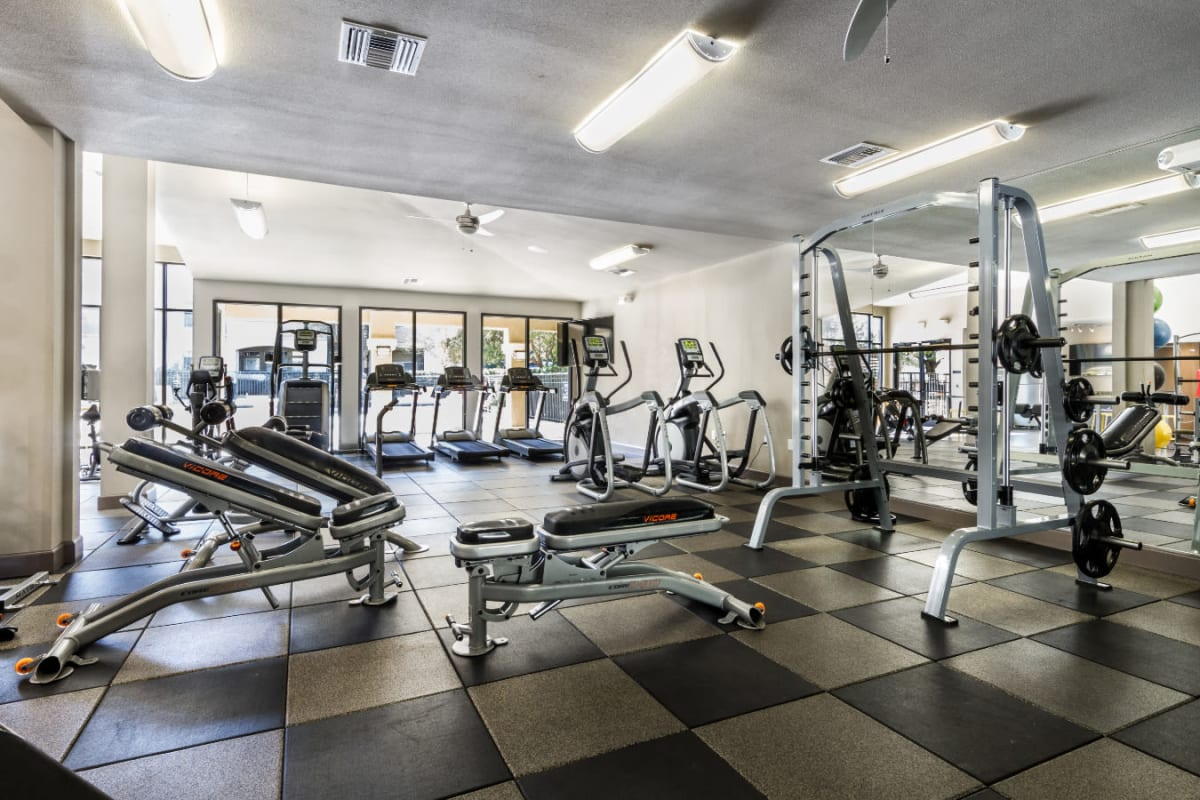 Indoor fitness center with multiple exercise machines and assisted weights section at Marquis at Barton Trails in Austin, Texas