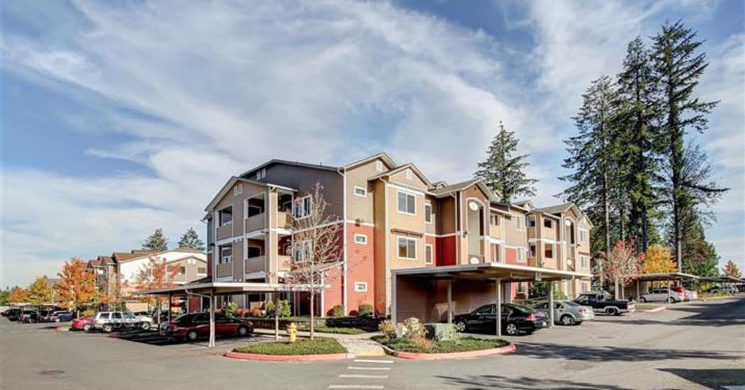 Resident buildings, parking, and mature trees at Woodland Apartments in Olympia, WA