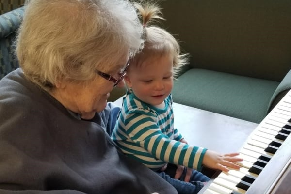 Resident and child play the piano at Ebenezer Ridges Campus in Burnsville, Minnesota.