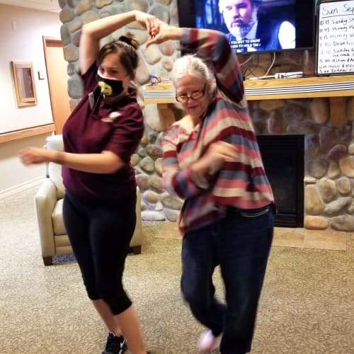 Resident and a masked caretaker dancing at The Oxford Grand Assisted Living & Memory Care in Wichita, Kansas