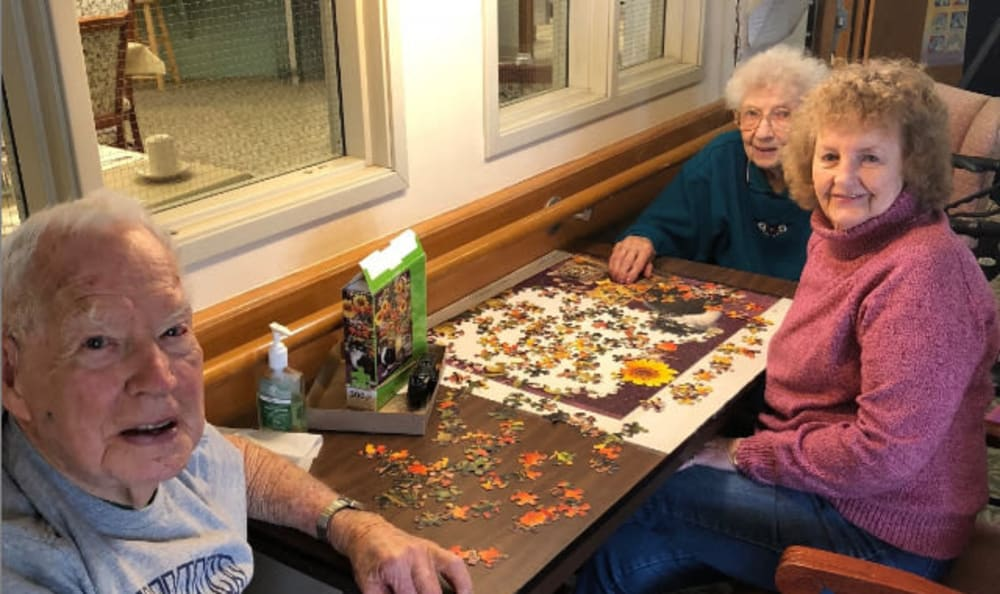 Three residents pass some time working on a puzzle together.