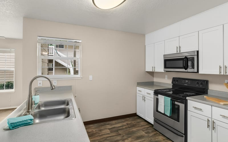 Newly renovated kitchen with white cabinets at Carriage Park Apartments in Vancouver, Washington