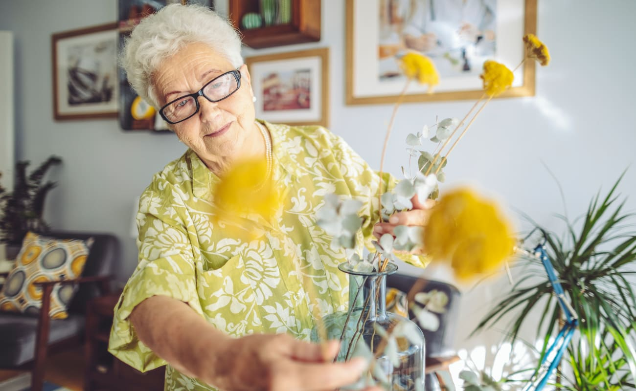 A resident putting flowers in a vase at Merrill Gardens at Tacoma in Tacoma, Washington.