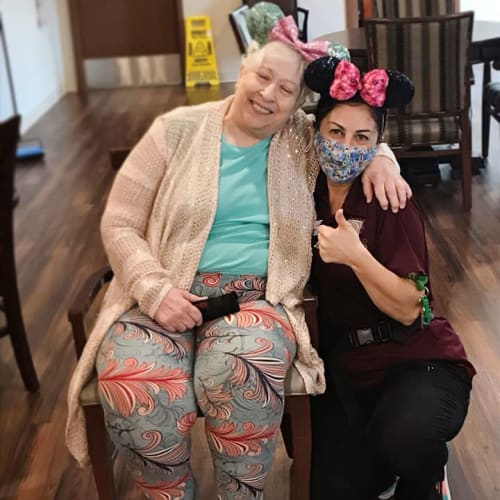masked caretaker side-hugging a seated resident at The Oxford Grand Assisted Living & Memory Care in McKinney, Texas