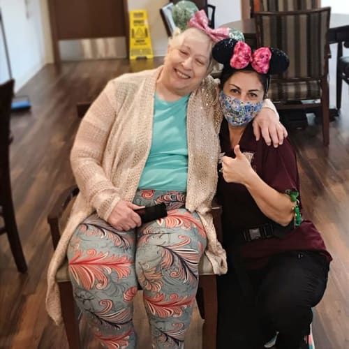 Masked caretaker hugging a resident at The Oxford Grand Assisted Living & Memory Care in McKinney, Texas
