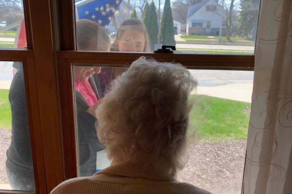 Resident watches a flag raising through the window at Ramsey Woods in Cudahy, Wisconsin.