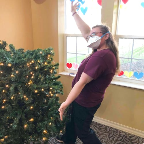 Team member posing next to a christmas tree at The Oxford Grand Assisted Living & Memory Care in Wichita, Kansas