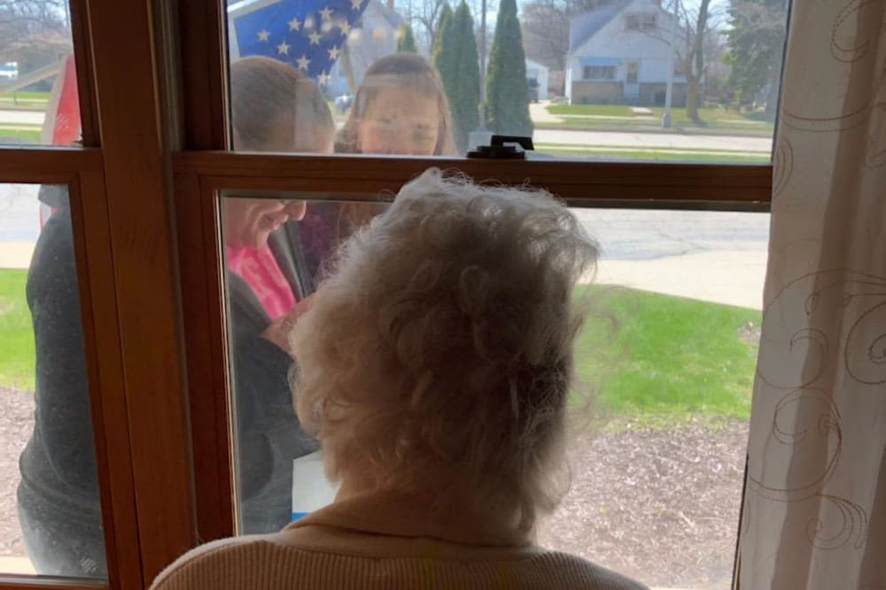 Resident watches through window as flag is raised at Ramsey Woods in Cudahy, Wisconsin.