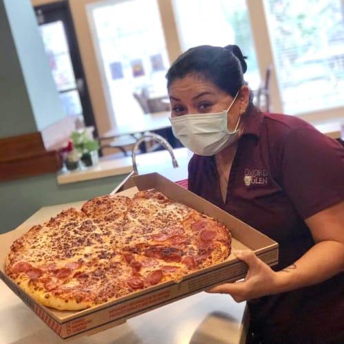 Team member saerving pizza at Oxford Senior Living in Wichita, Kansas
