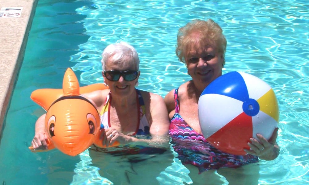 Two residents in the pool with pool toys at The Palms at LaQuinta Gracious Retirement Living in La Quinta, California