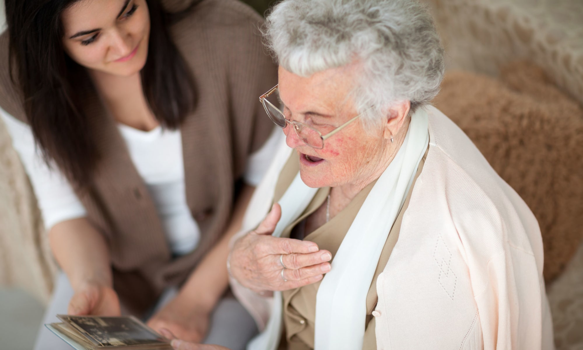 Caregiver and resident look at pictures together at Broadwell Senior Living in Plymouth, Minnesota