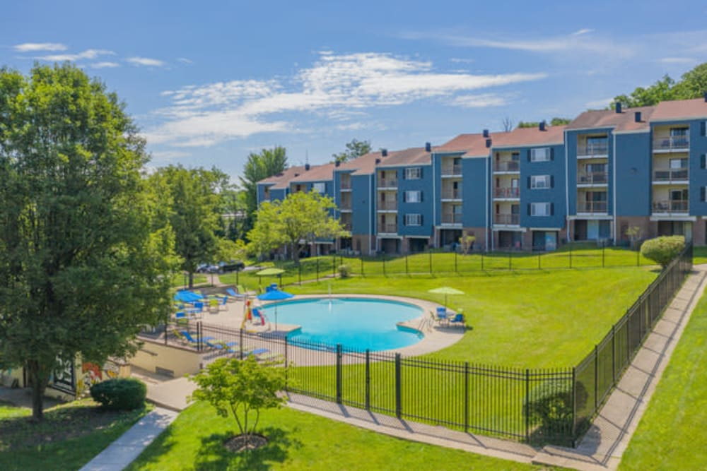 Swimming pool area surrounded by lush green grass at Eagle Rock Apartments at Towson in Towson, Maryland