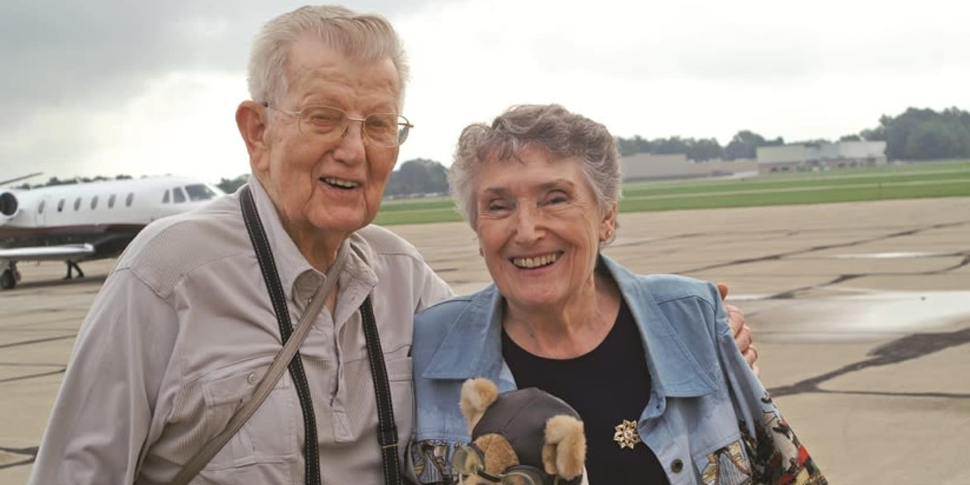 Two residents from Heritage Meadows Gracious Retirement Living in Cambridge, Ontario posing in front of a plane