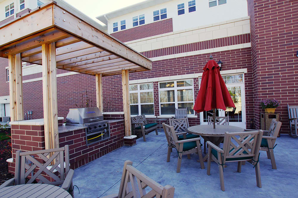 Bbq area with tables and umbrellas at Oak Hill Supportive Living Community