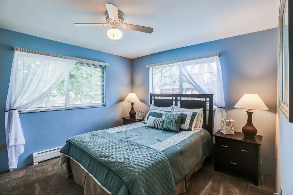 A bedroom, well-lit by large windows, at Four Seasons Apartments in Erlanger, Kentucky