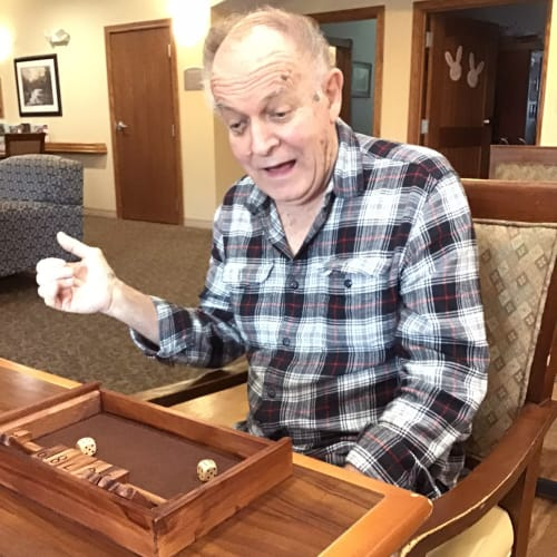 A resident playing a dice game at a wooden table inside Glen Carr House Memory Care in Derby, Kansas