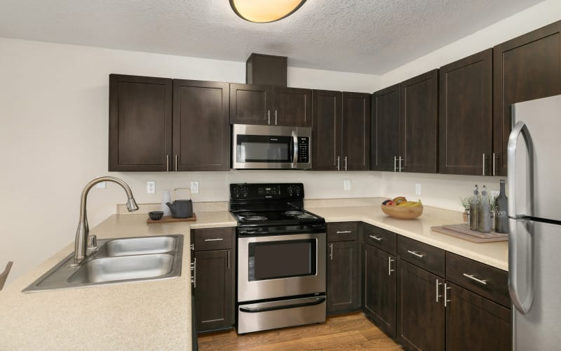 Beautifully renovated kitchen with espresso cabinetry and stainless steel appliances at Carriage Park Apartments in Vancouver, Washington