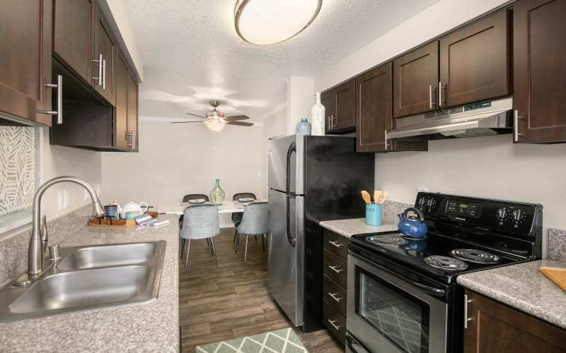 Fully equipped kitchen with brown cabinets, stainless steel appliances and a view of the dining room at Walnut Grove Landing Apartments in Vancouver, Washington