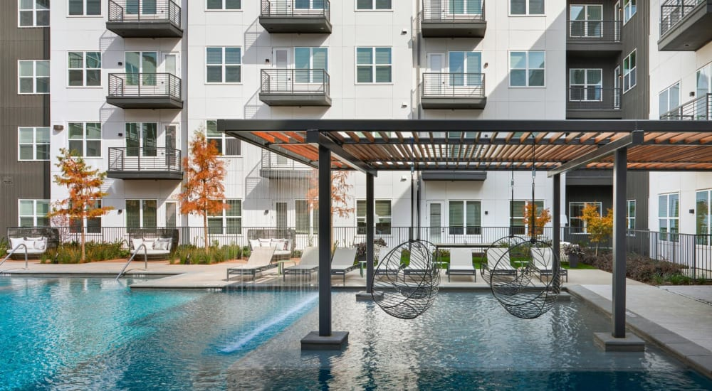 Pergola and hanging chairs over a portion of the swimming pool at 4600 Ross in Dallas, Texas