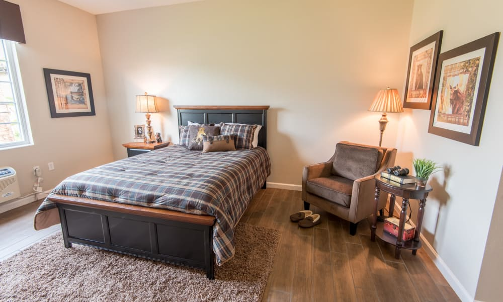 Spacious resident bedroom with hardwood flooring at Inspired Living Bonita Springs in Bonita Springs, Florida