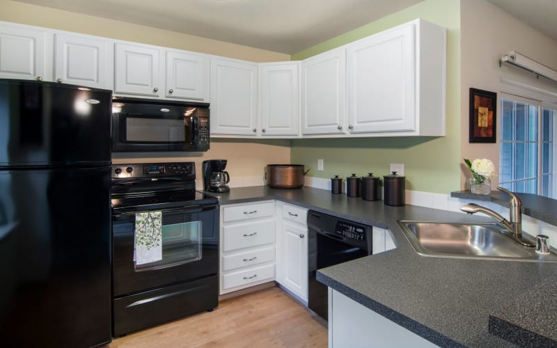 Black appliances and white cabinets in a renovated kitchen at Autumn Chase Apartments in Vancouver, Washington