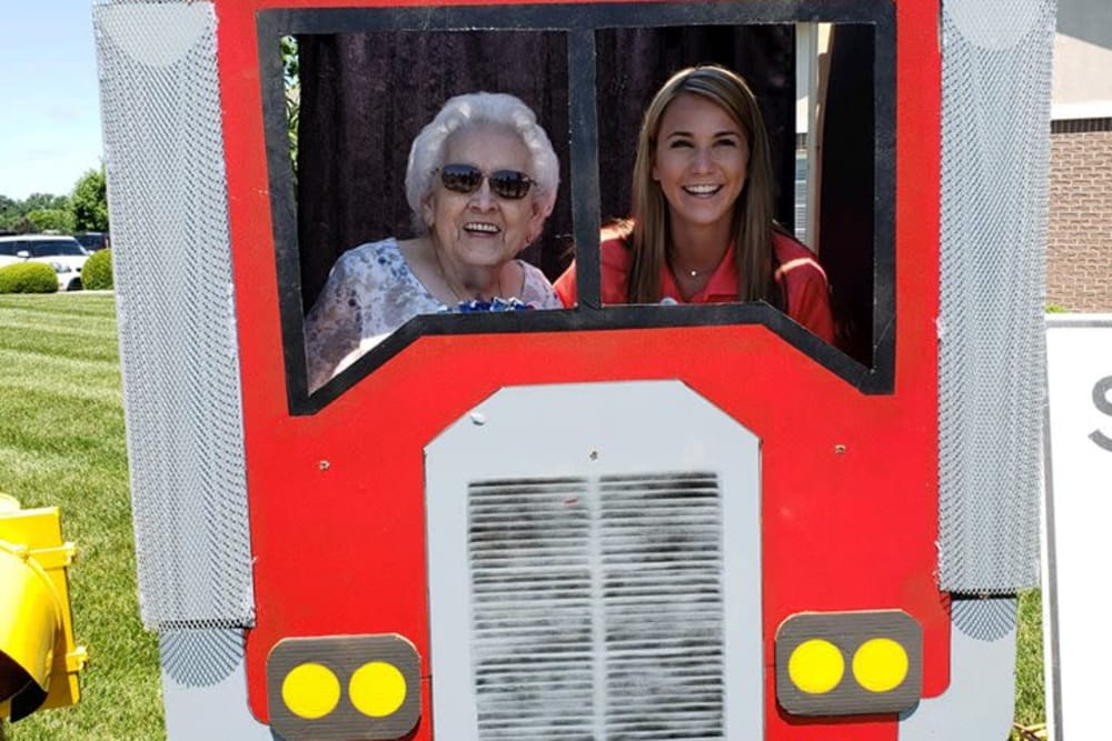 A female resident and staff member posing inside a semi truck photo prop at St. Andrews Health Campus in Batesville, Indiana