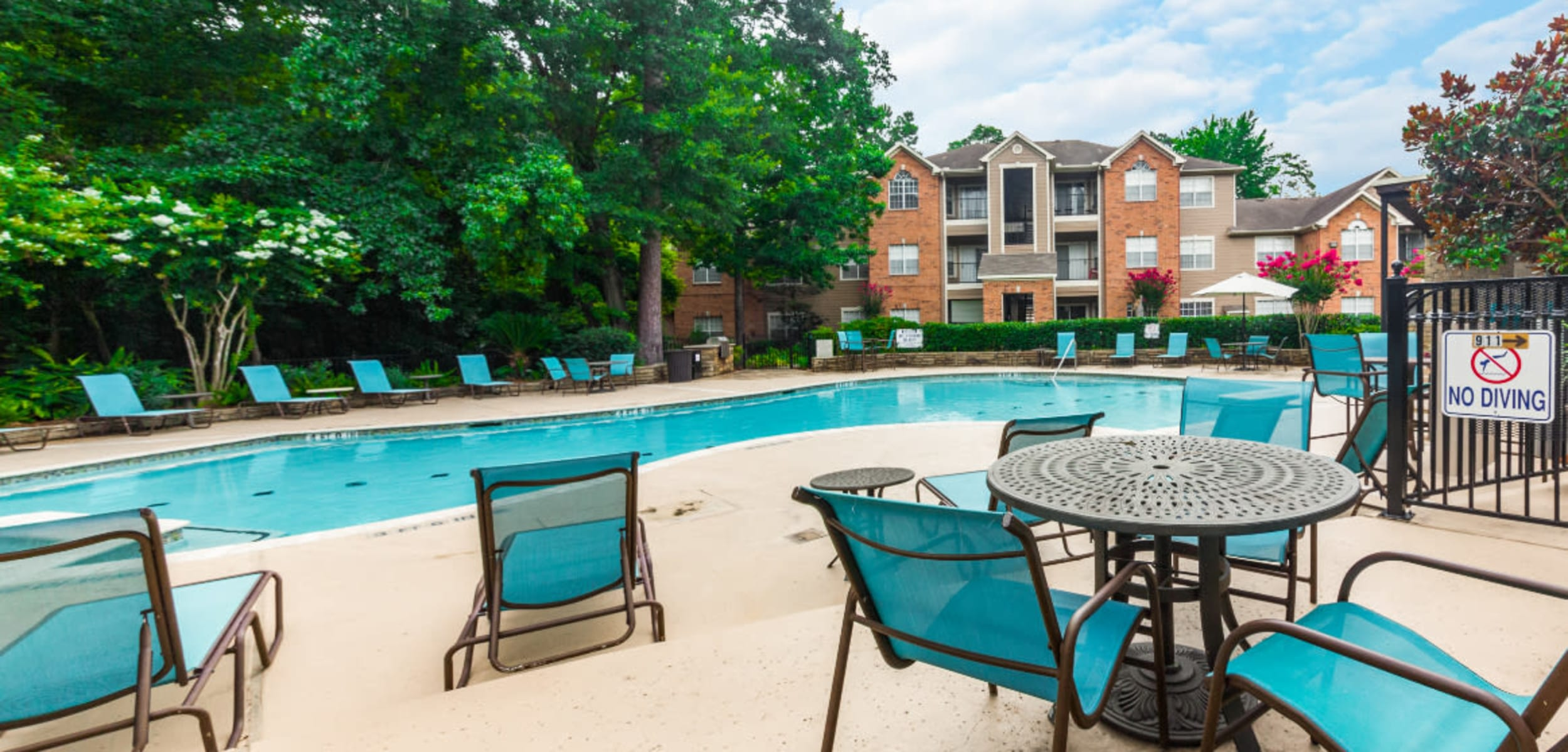 Overlooking pool and patio lounge chairs and tables at Marquis at Kingwood in Kingwood, Texas