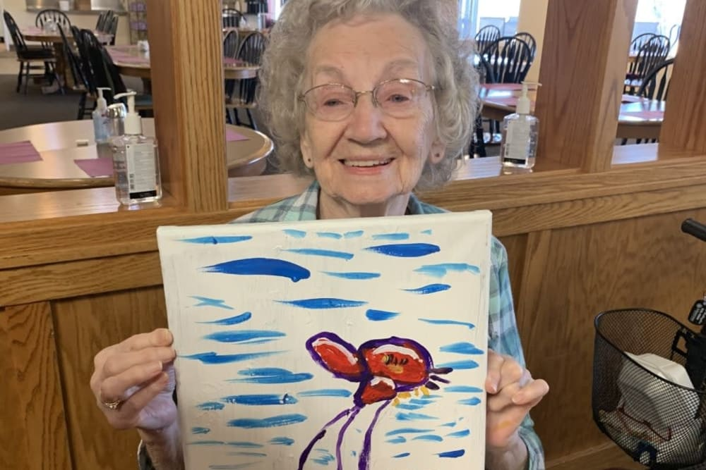 A resident showing off her painting at The Wellington in Minot, North Dakota