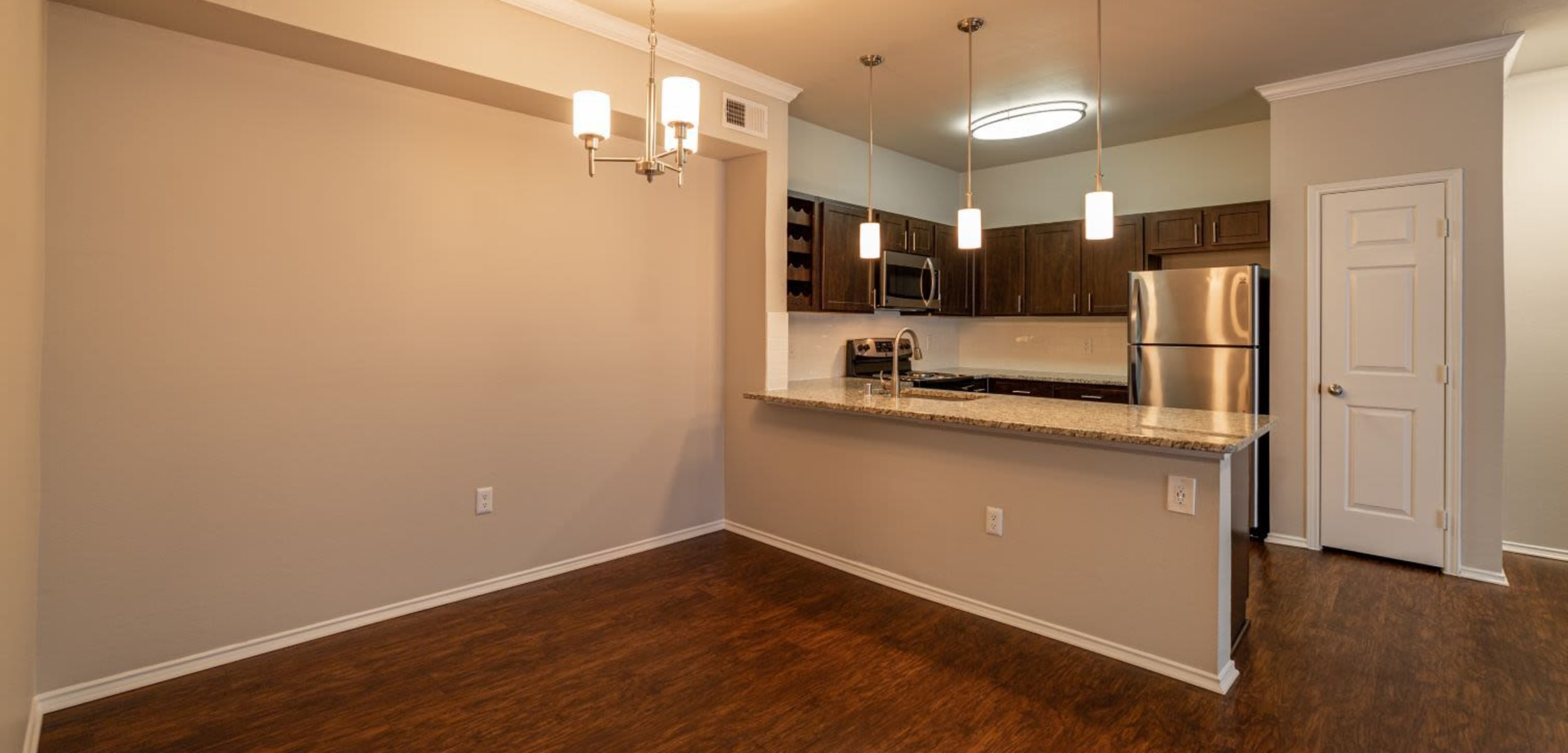 Dining area and kitchen with wood style floors at Marquis at Stonebriar in Frisco, Texas