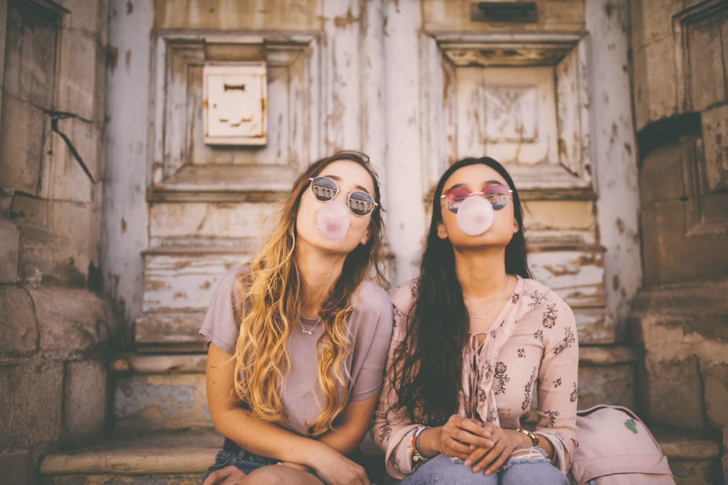 Teenage girls blowing bubbles with pink bubble gum in antique city streets near 23Hundred at Ridgeview in Plano, Texas