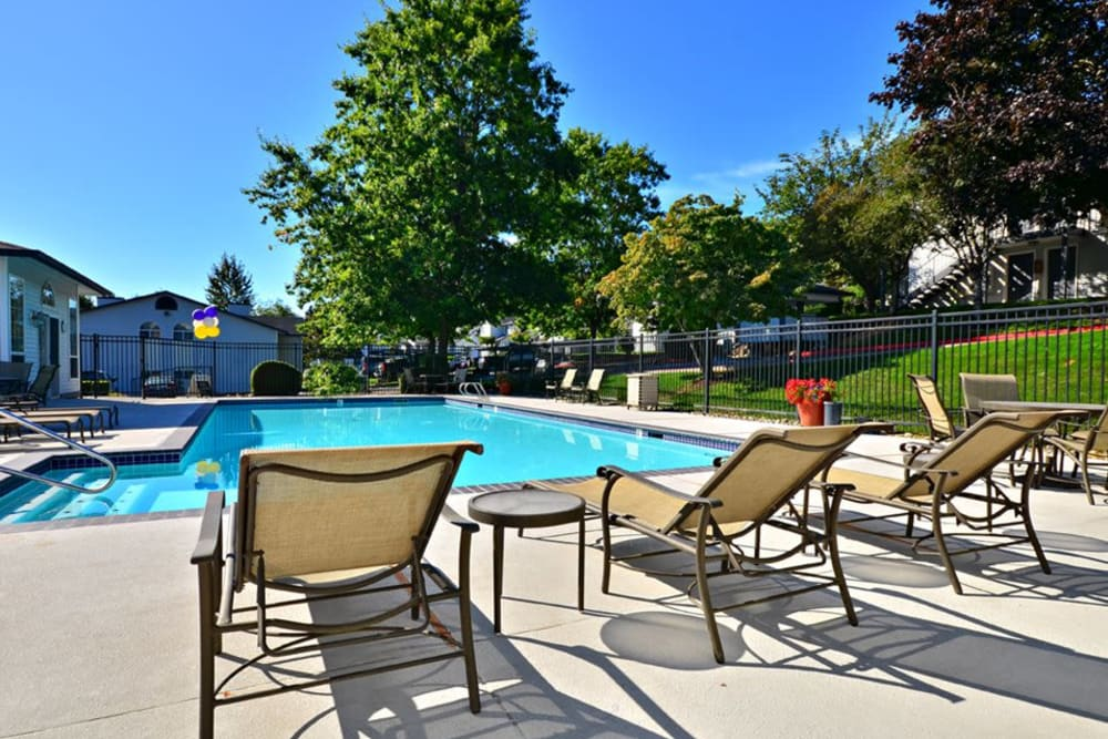 Beautiful resort-style swimming pool with lounge chairs at Wellington Apartment Homes in Silverdale, Washington